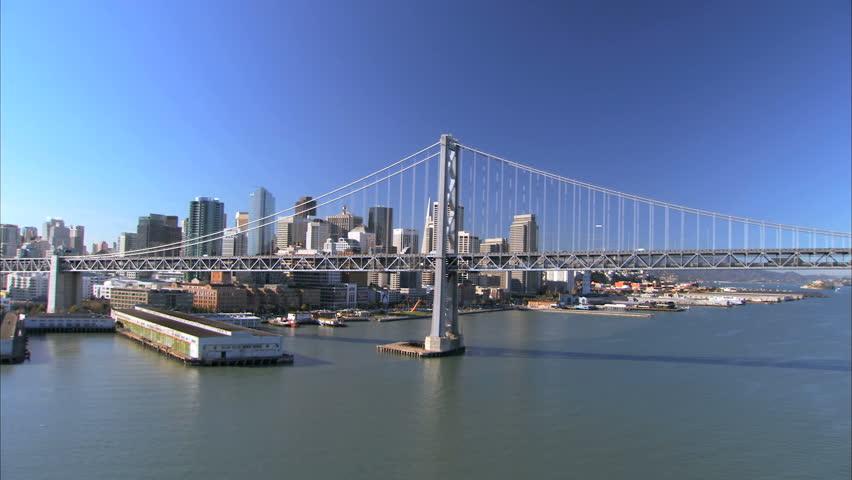 Low aerial view of Oakland Bay Bridge & skyscrapers of San Francisco, USA