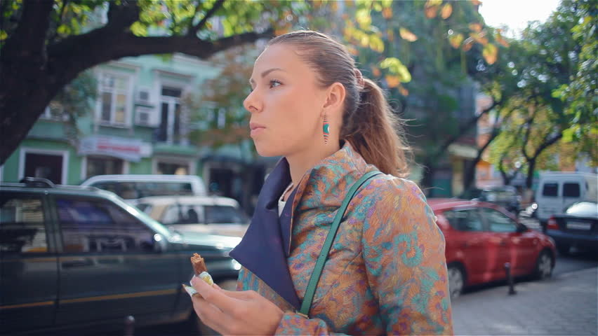 Young, beautiful, fashionable girl goes to a European city and eating a chocolate bar