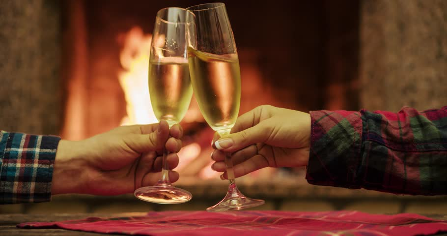 Couple Toasting With Champagne By The Cozy Fireplace Close Up