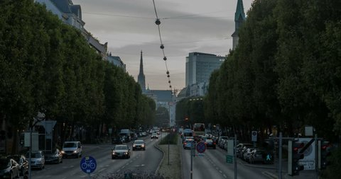 Cars are driving by the traffic hub of Praterstern in Vienna. In the background one can see the St. Stephans Cathedral in the evening mood.