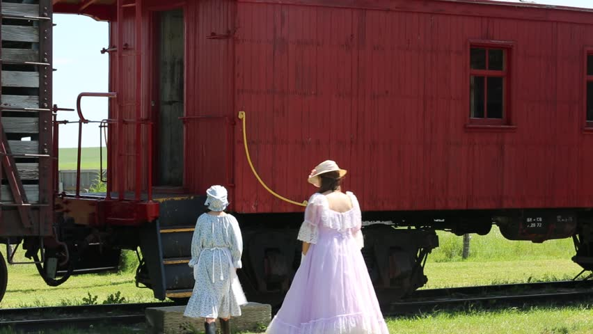 Deadwood, South Dakota, July 2014: Young girls in western era clothing enter a vintage train caboose at a tourist town near Deadwood, South Dakota, July 2014.