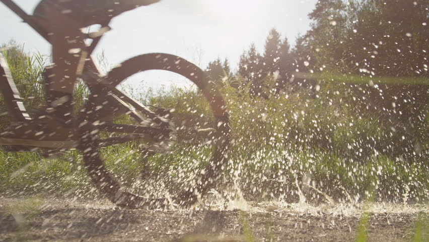 SLOW MOTION: Biker rides through puddle and splashes the camera | Shutterstock HD Video #7465522