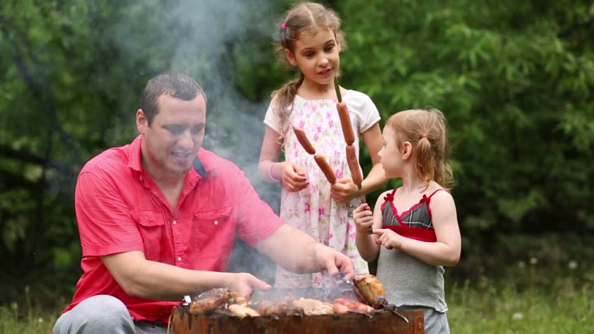 Family of three makes barbecue on the grill at green lawn.