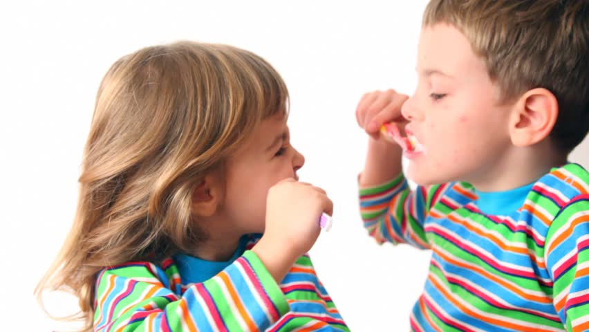 boy and girl brush teeth looking against each other, then turn and smile