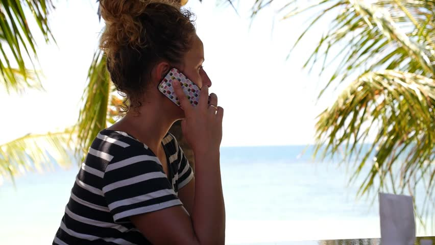 Young Woman in Sailor T-shirt and Curly Hair Talking by Phone on a Sunny Beach. Vacation on Ko Pha Ngan. Thailand. HD, 1920x1080.   Shutterstock HD Video #7508488