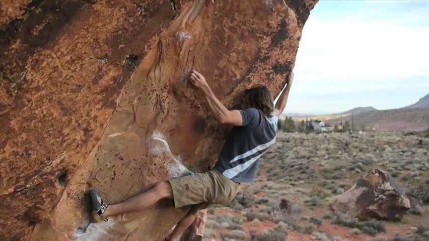 A rock climber climbs up a big boulder