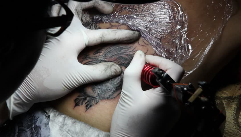 tattooer showing process of making stock footage video (100% royalty