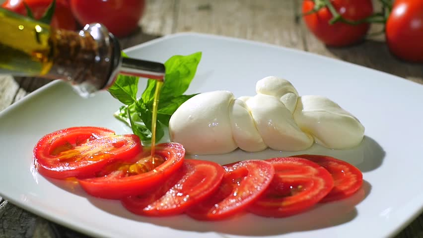pouring olive oil over caprese salad