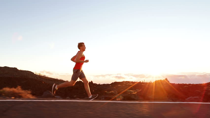 Running runner man athlete training outdoors exercising on mountain road at sunset in amazing landscape nature. Fit handsome athletic male working out for marathon run outside in summer.