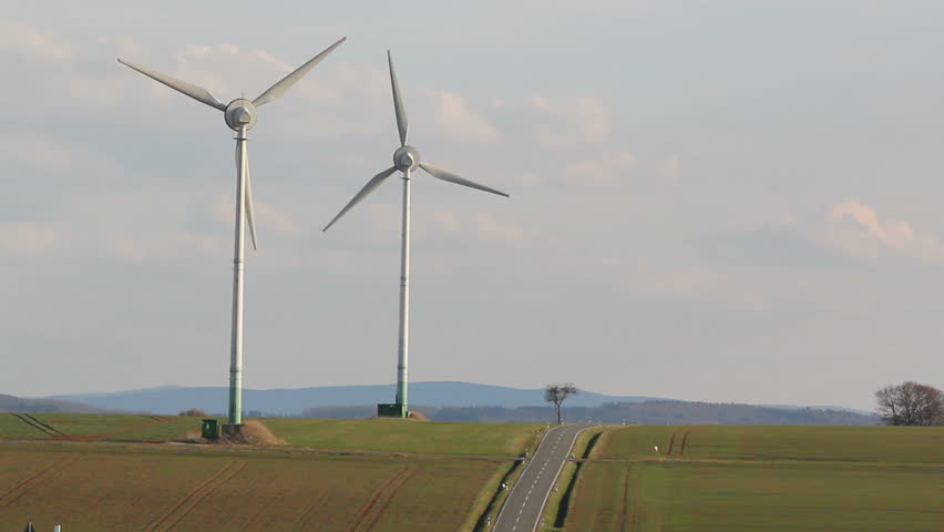 two wind turbines near a road in rural German landscape