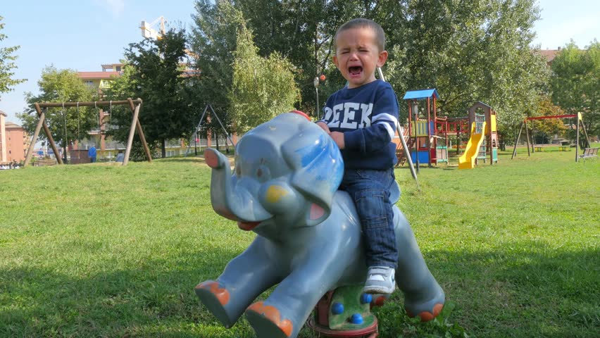 child on a rocking animal cries because he wants the pacifier