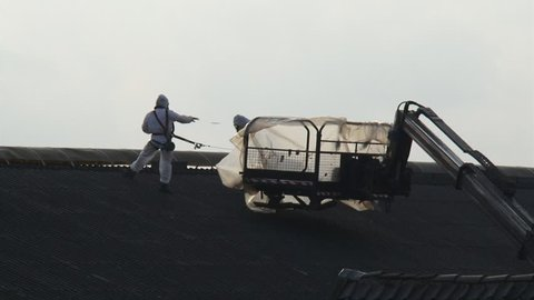 Removal of asbestos building components wearing protective asbestos clothes