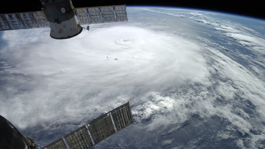 Large typhoon / hurricane framed by two orbiting satellites.