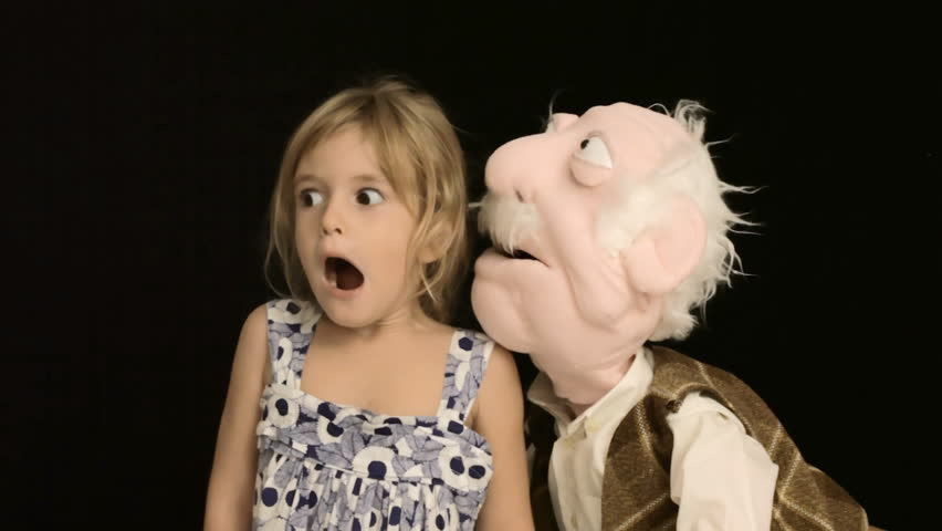 The puppet of an old man whispers a secret in the ear of a cute little girl.