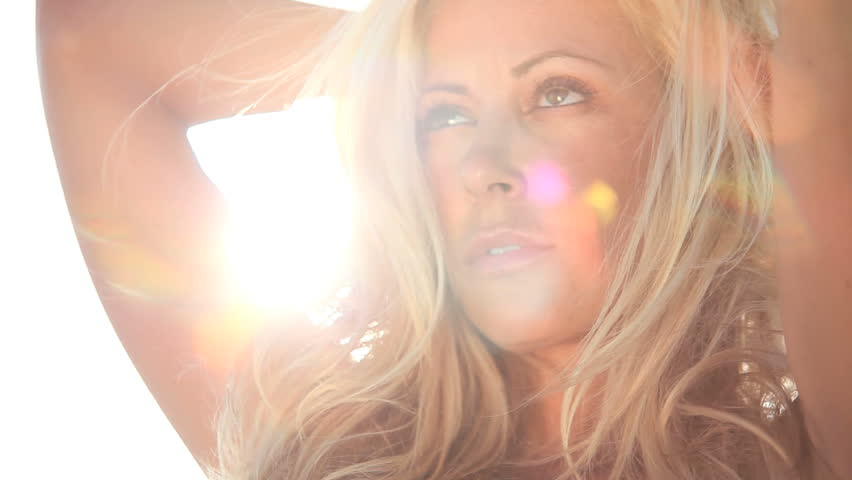 Portrait of sensual blonde female with windswept hair & sun shining behind