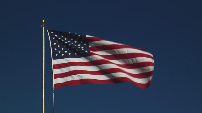 real United States of America flag flying on flagpole against clear blue sky - HD, no audio, zoom in