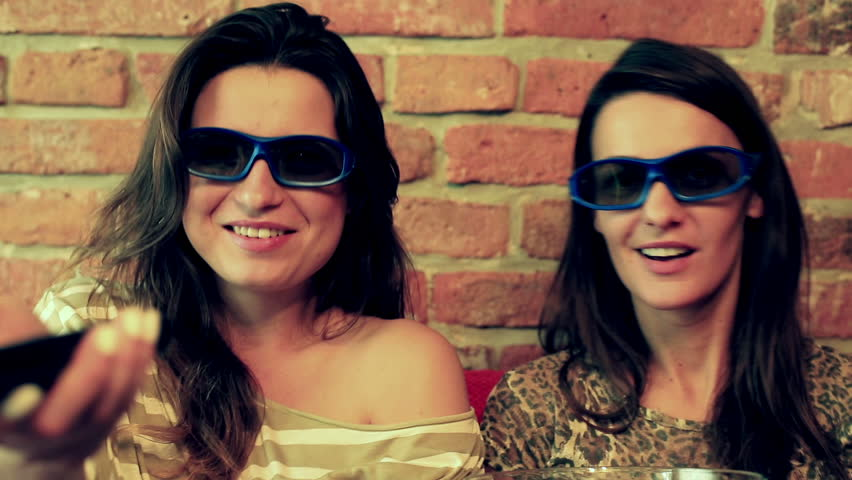Women laughing while watching movie in 3d glasses and eating popcorn  | Shutterstock HD Video #7669648