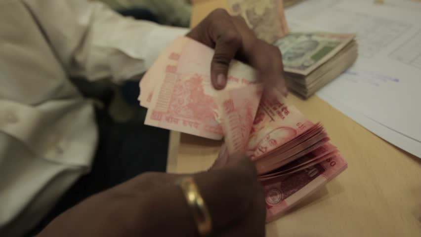 Indian man with golden ring quickly counts a large wad of 20 rupee indian currency bank notes in an office | Shutterstock HD Video #7698508