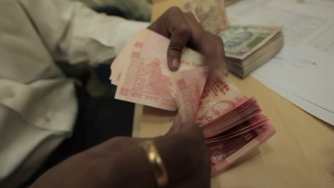 Indian man with golden ring quickly counts a large wad of 20 rupee indian currency bank notes in an office