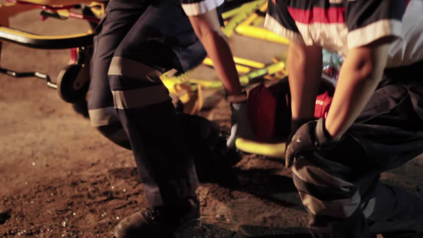 Paramedics helps an injured woman moving the stretcher from accident place