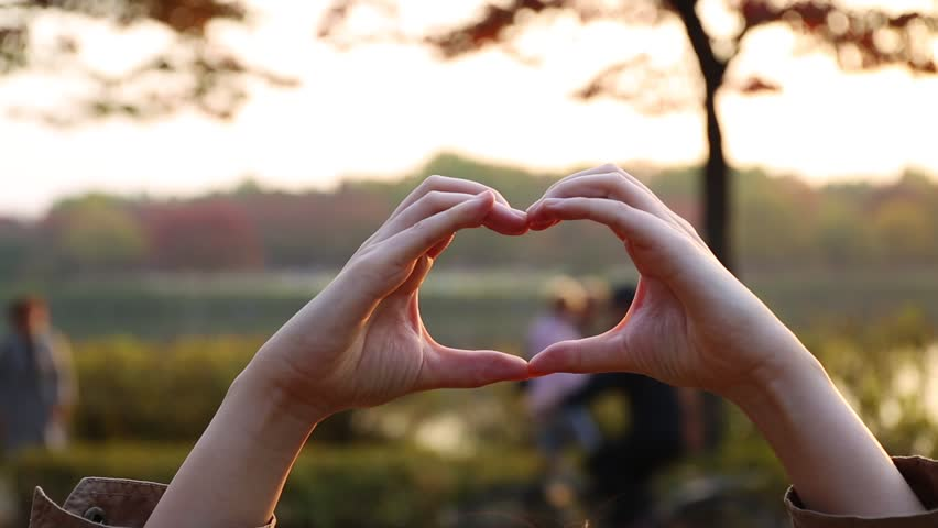 Female hands making heart shape gesture against autumn park with people walking around