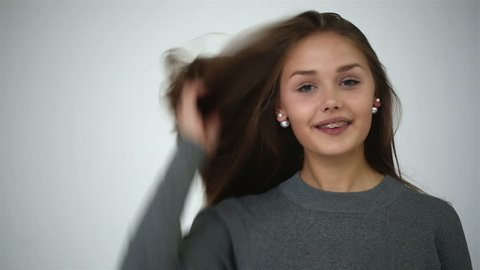 Young girl with braces on teeth throws back her head and appears in the frame. Video shot in the studio. Professional light. Professional model.