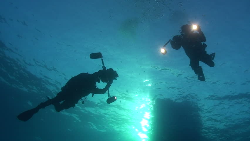 Low angle silhouette view of two scuba divers with underwater cameras.   Shutterstock HD Video #777148