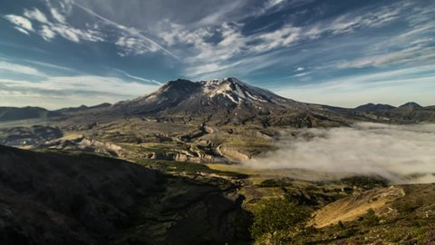 Time Lapse scene of a layer of fog moving in below Mount St. Helens before moving out as a series of alt cumulus clouds move across the mountain.