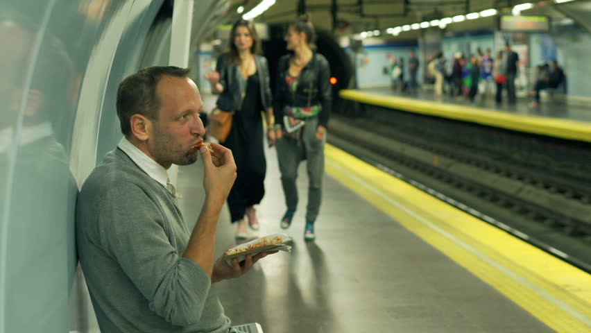 Man eating croissant in the metro station, steadycam shot