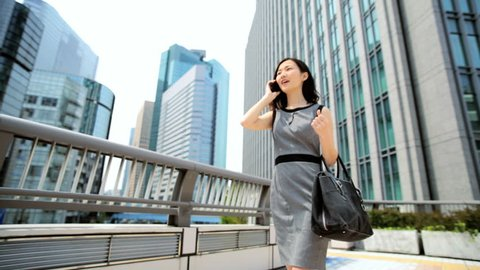 Ambitious ethnic Asian Japanese girl advertising business manager outdoors downtown buildings wireless hotspot smart phone connection