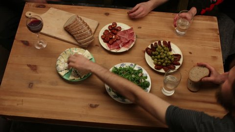 Preparing and eating food with friends time-lapse (antipasto, bread, salad, ham, cheese, olives, dried tomatoes...), 4K, top view