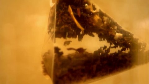Pyramid tea bag dropped into the hot water turning it into orange color. Extreme closeup.