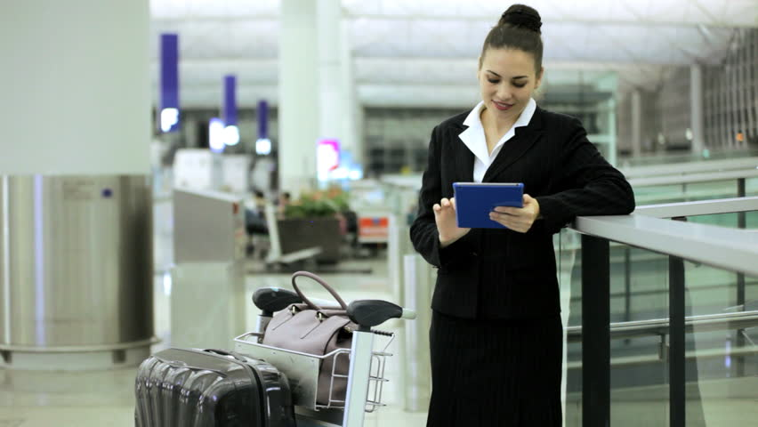 Female Caucasian businesswoman consultant business suit airport departures travel destination professional wireless tablet technology communication | Shutterstock HD Video #7854658