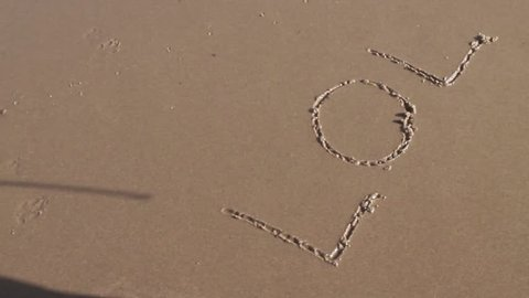 Lol written in sand with shadow of stick above