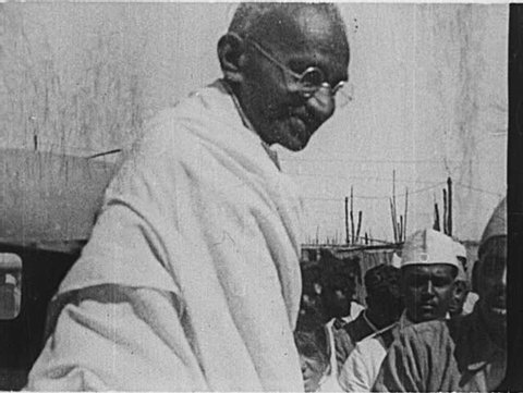 INDIA- CIRCA 1930: A large crowd greets Gandhi as he steps out of a car and acknowledges its members.  Men crowd around him, offering gifts and flowers, praying, and bowing.