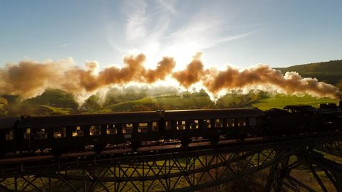 epic aerial view of steam engine train crossing bridge at sunset magic hour. old locomotive