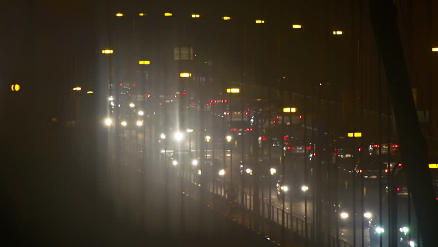 Timelapse version of traffic at night as people flee in droves from their workplaces in San Francisco and others stream into the city via the Golden Gate Bridge. #7882138