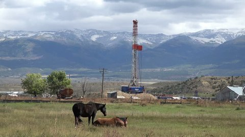 MORONI, UTAH - OCT 2014: Oil exploration well rural farming community. Gas and oil pricing at near record price exploration continues to areas never before explored. Farm land used for industrial use.