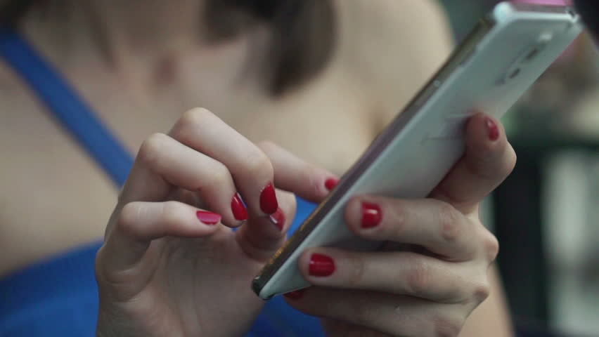 Closeup of woman hands texting on smartphone in city