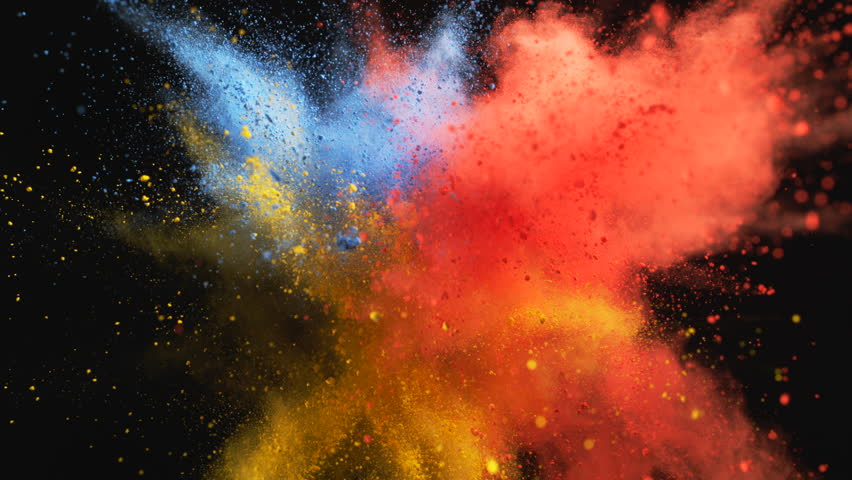 Red, yellow and blue powder/particles fly after being exploded against black background. Shot with high speed camera, phantom flex 4K. 4K 30fps. Slow Motion.