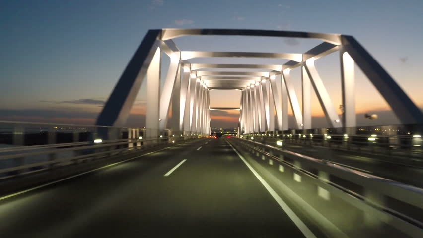 Driver's POV driving through the illuminating Tokyo Gate Bridge during twilight. 4K variation available at Clip ID 9127304, night version Clip ID 6171539. Sun setting over the airport and Tokyo Bay.