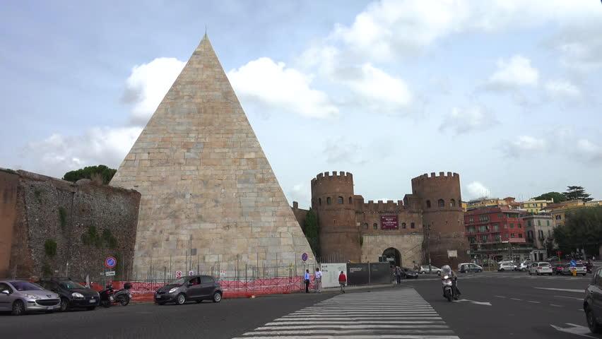 ROME - OCT. 2014: Cars pass through Porta San Paolo past Pyramid of Cestius, or Piramide; circa 18 BCE –12 BCE, later incorporated into Aurelian Walls, on left. Museo della Via Ostiense in castle.