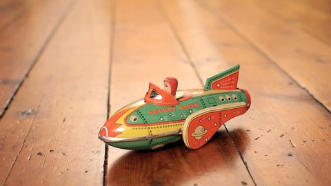 BOSTON, MA - April 7: Old vintage toy rocketship rolls on wooden floor on April 7, 2014. Tinplate was used in the manufacture of toys beginning in the mid-19th century.