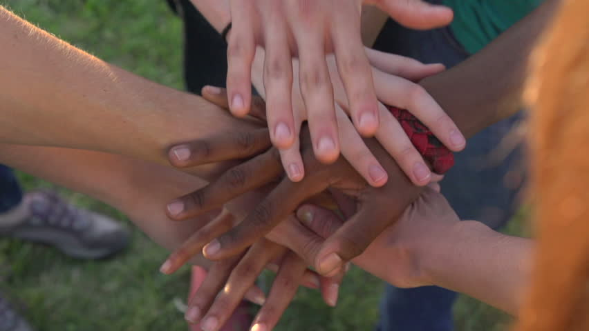 A close-up in slow motion, of hands of all races and colors stacked together one by one in unity and teamwork and then raised. #7969738