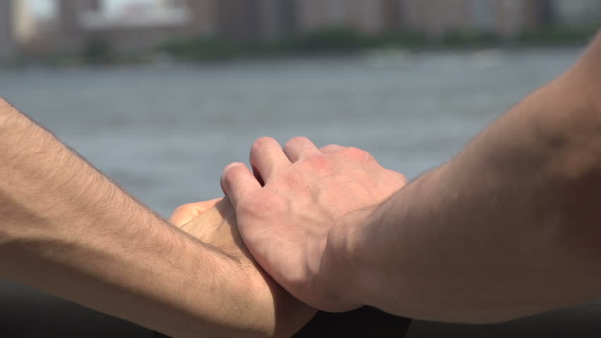 A close-up of a Caucasian gay man's hand on a bridge. A second man's hand comes into shot and squeezes it affectionately.