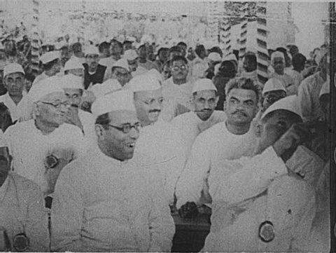 INDIA- CIRCA 1930: Long, aerial shots of crowds of Indian men in mundus and topis on a street. Indian men and boys walk alongside Gandhi.