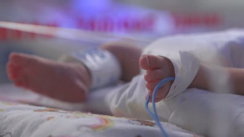 Baby foot in the intensive care hospital bed after the birth
