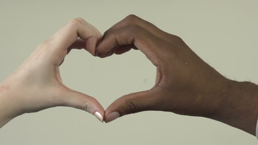 A close-up of an interracial couple - a black man and a white woman. In the background, they form a hear with their hands, while in the foreground they share a kiss.