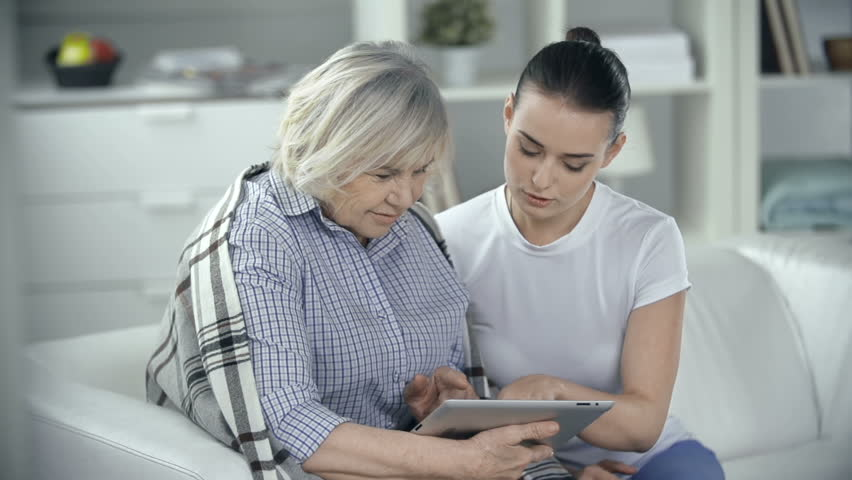 Senior woman wrapped in comfortable rug watching photos on the digital tab device