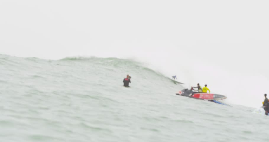 PERU - JULY 03, 2014: Big Wave World Tour- Jet skis carrying surfboards with male big wave surfer competing in background. Boat angle. | Shutterstock HD Video #8103238